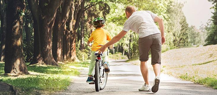 father pushing child on bike duluth
